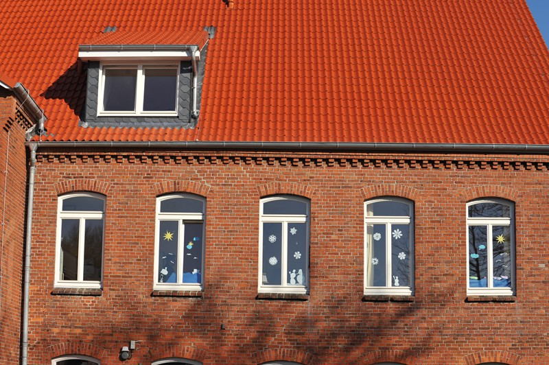 Individuelle Fenster in einem Backsteinhaus