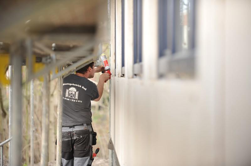 Arbeiter bei der Fensterabdichtung